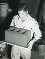 Al Litvin holding the all-clay construction block developed at Armour Research Foundation, Illinois Institute of Technology, Chicago, Illinois, ca. 1956