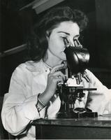 Trudy Cheskis using microscope, Illinois Institute of Technology, Chicago, Illinois, 1947